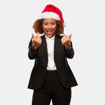 来ることを誘ってchirstmasのサンタの帽子を身に着けている若いビジネス黒人の女性