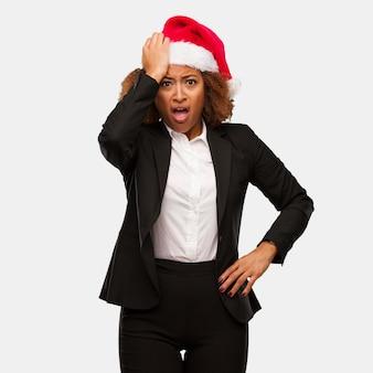Chirstmasのサンタの帽子を身に着けている若いビジネス黒人の女性は、心配し、圧倒
