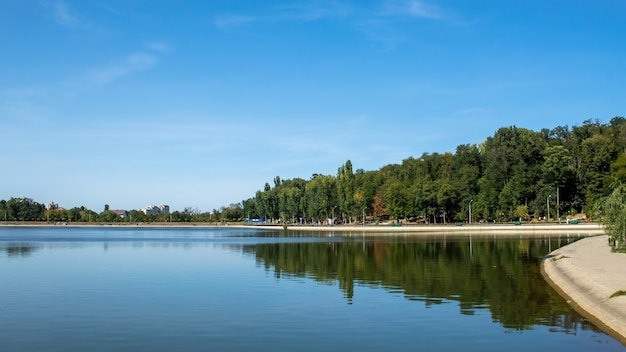 モルドバ、キシナウ-2020年9月20日:歩く人々がいるヴァレアモリラー公園、水に映る緑豊かな木々のある湖