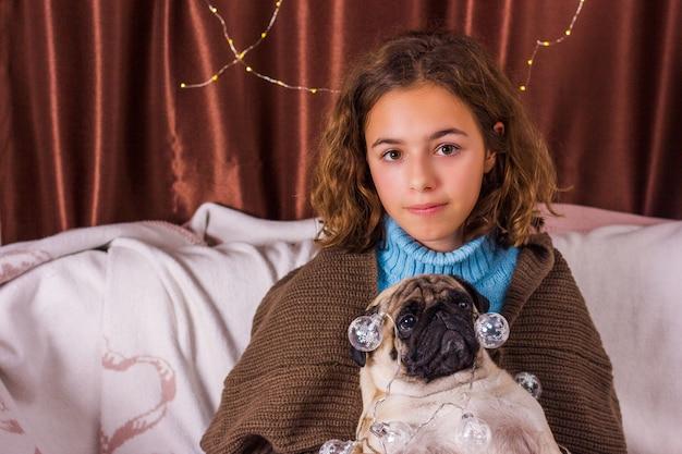 Chistmas garland on pug dog. charming girl with a very funny dog pug. curly girl hugs a pug