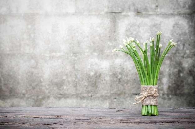 Chives flower or chinese chives on wooden table with old brick wall background