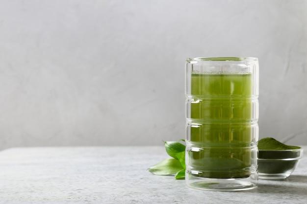Здоровый напиток хлореллы в стекле на сером фоне.