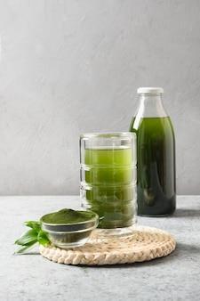 회색 배경에 유리에 클로렐라 건강 음료.