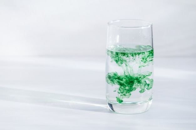 Chlorophyll in glass of water. copy space, sunlight.