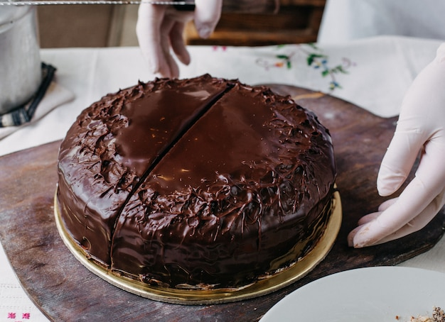 Choco cake getting sliced yummy delicious round whole designing with kumquats nuts