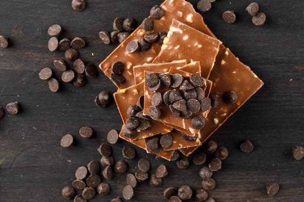 Шоколадные капли с шоколадными батончиками на деревянном столе