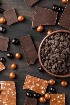 Choco падает с chocoballs и шоколадные батончики в миску на деревянный стол