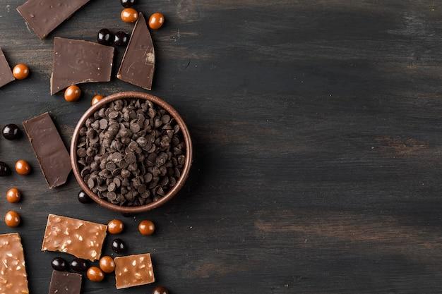 Шоколадные капли с шоколадными шариками и шоколадными батончиками в глиняной миске на деревянном столе