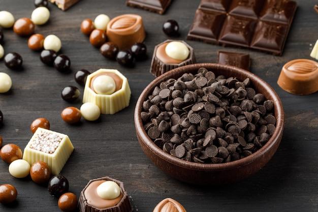 Шоколадные капли с шоколадными шариками, шоколадными батончиками и карамелью в глиняной миске на деревянном столе