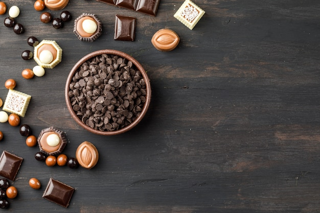 Choco drops with chocoballs, choco bars and caramel in a clay bowl