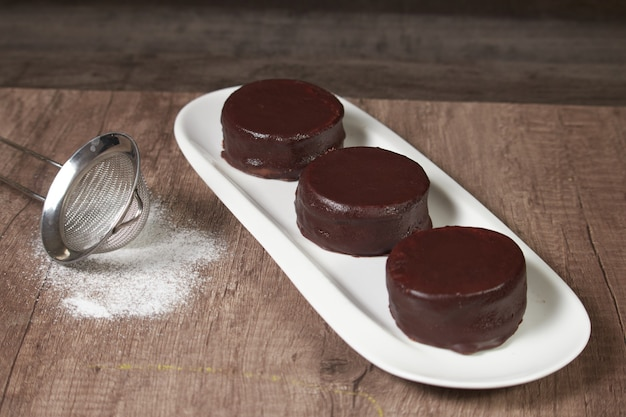 Chocolate alfajor on a white platter, with fresh blueberries, sugar and several. on a wooden table and dark background
