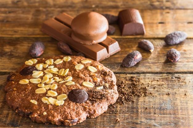 ダークトーンの木製のチョコレートアーモンドチップクラッカーとカップケーキ