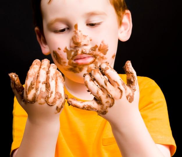 チョコレートとミルクチョコレートに完全に塗られた赤ちゃん