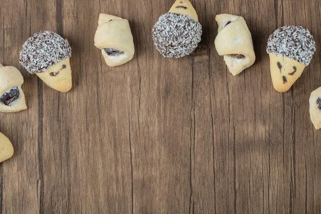 Шоколадное и масляное печенье подряд на деревянном столе.