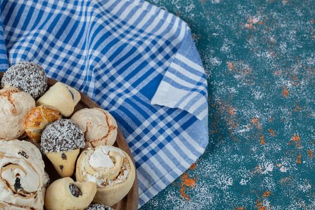 Шоколадное и масляное печенье на голубом клетчатом полотенце.