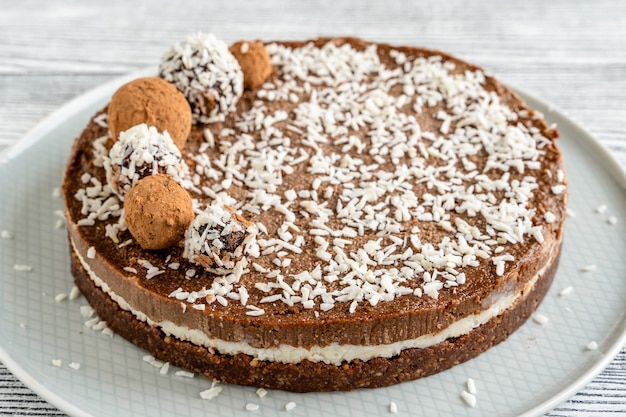 白い木の上のチョコレートとココナッツのケーキ。