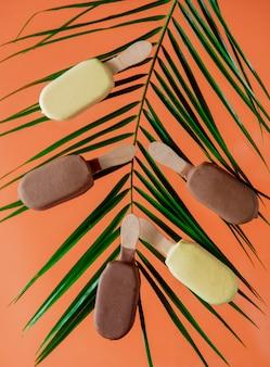 손바닥으로 초콜릿과 크림 아이스크림 오렌지 벽에 나뭇잎.