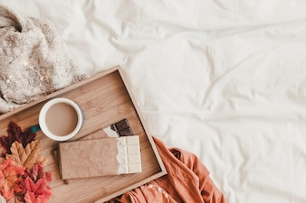 Chocolate and leaves near coffee on bed