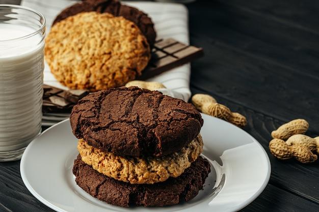 暗い木製のテーブルにチョコレートとオート麦のクッキー