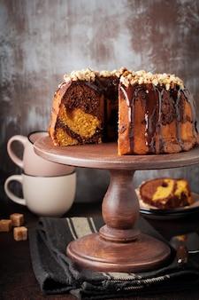 어두운 콘크리트 표면에 초콜렛 유약과 호두가 들어간 초콜릿과 호박 번트 케이크