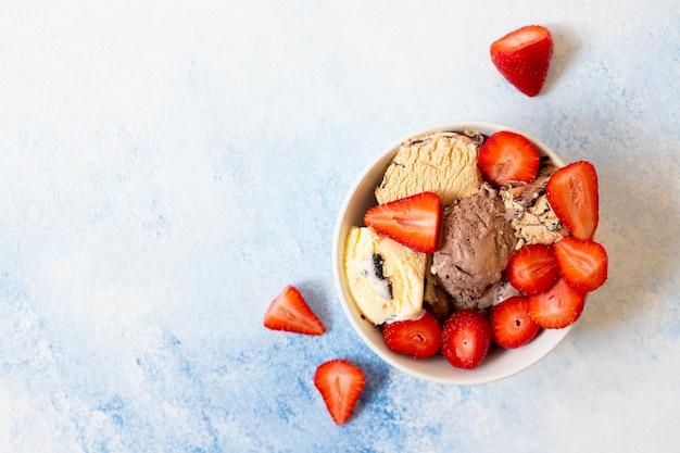 新鮮なイチゴと白いボウルにチョコレートとバニラのアイスクリーム。明るい青の背景。上面図。コピースペース