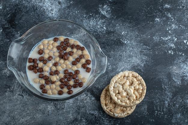 Шоколадные и пшеничные шарики в стеклянной миске с хрустящими хлебцами.