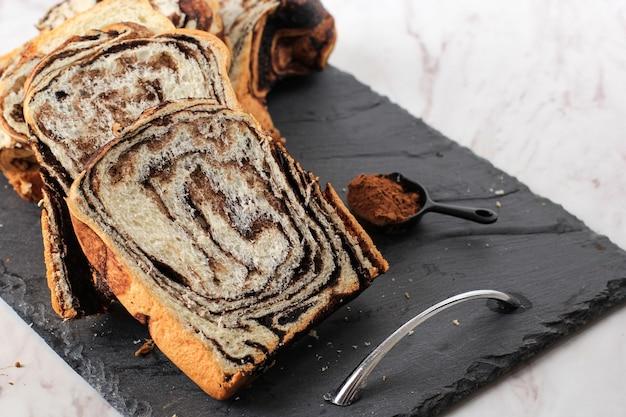 Шоколадная бабка или булочка. домашнее сладкое десертное тесто - шоколадный вихревой хлеб с мраморной текстурой. нарезанный на белом фоне