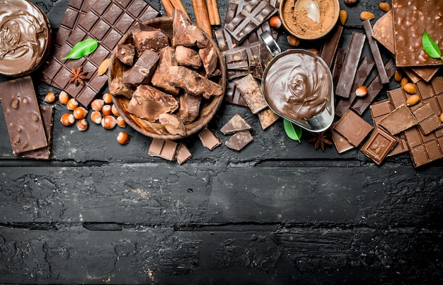 Chocolate background. various assortment of chocolate with paste. on black rustic background.