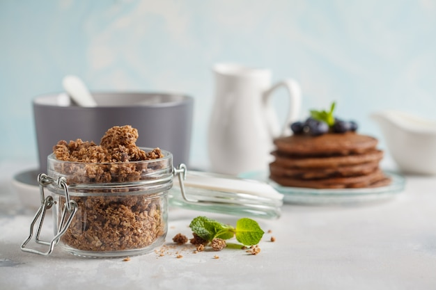 Chocolate baked granola in a glass jar, chocolate pancakes and milk. healthy breakfast concept.