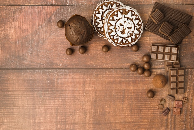 Chocolate ball; bar; muffins and baked cookies on wooden backdrop