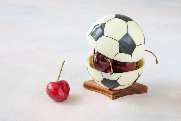 Chocolate ball for european football with cherry berries inside. modern dessert concept for healthy watching of football matches with a delicious snack