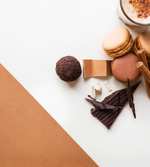 Chocolate ball; macaroons and coffee glass with ingredients on white backdrop