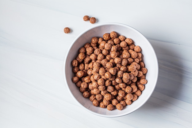 Шоколадные шарики кукурузные хлопья в белом шаре, белом фоне. концепция питания завтрак.