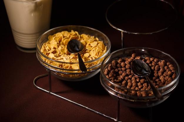 ボウルにチョコレートボールとテーブルにミルクの水差しとコーンフレーク。健康的な朝食