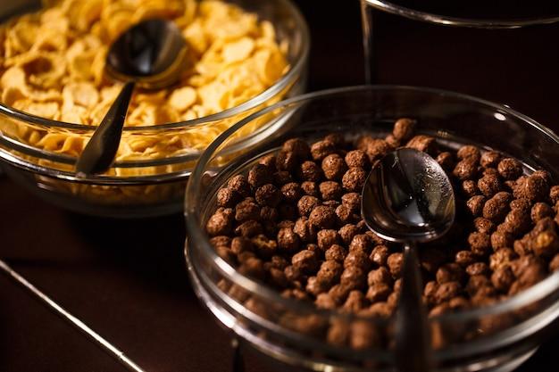 ボウルにチョコレートボールとテーブルにスプーンでコーンフレーク。健康的な朝食