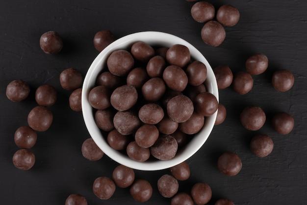 검은 색 표면에 흰색 그릇에 초콜릿 공입니다.