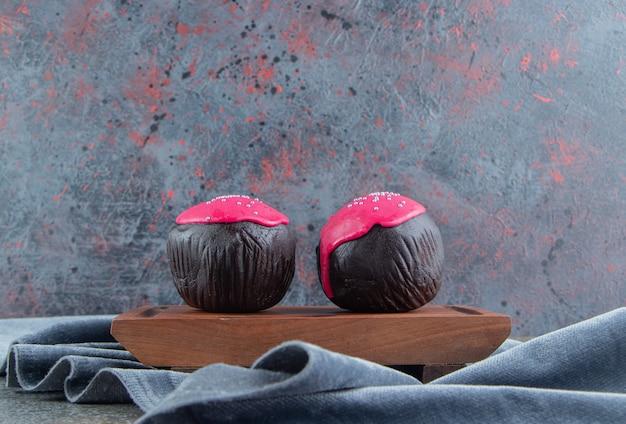 나무 보드에 분홍색 유약 초콜릿 볼