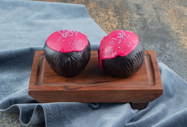 Palline di cioccolato con glassa rosa su tavola di legno