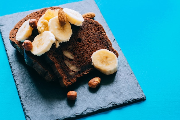 Chocolate banana bread on a black slate, with bananas