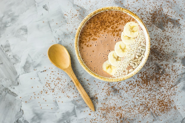 Chocolate-banana smoothies in a bowl on a gray concrete background