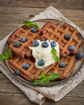 Chocolate banana waffles with blueberries, on dark wooden old table. side view, vertical