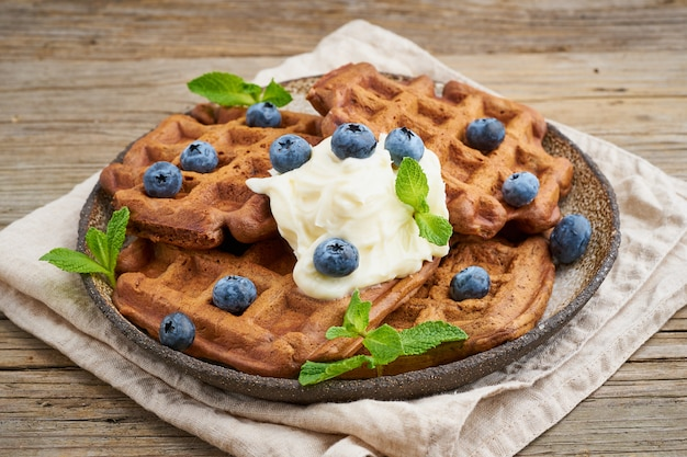 Chocolate banana waffles with blueberries, on dark wooden old table. side view