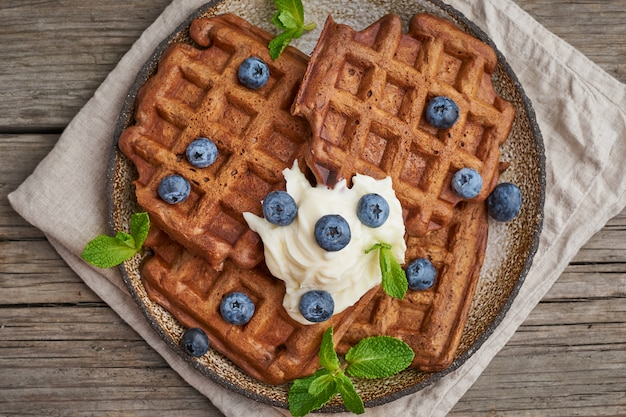 Chocolate banana waffles with blueberries, on dark wooden old table. top view, close up