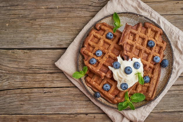 Chocolate banana waffles with blueberries, on dark wooden old table. top view, copy space