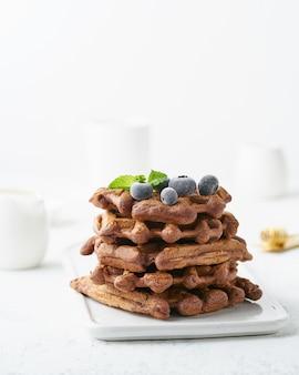 白いテーブルの上のブルーベリーとチョコレートバナナワッフル。側面図、垂直