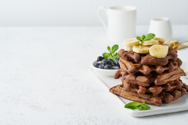 白いテーブル、コピースペース、サイドビューにメープルシロップとチョコレートのバナナワッフル。