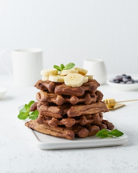 白いテーブル、サイドビュー、垂直にメープルシロップとチョコレートのバナナワッフル。甘いブランチ