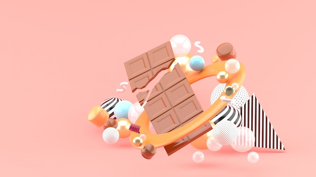 Chocolate bar among the colorful balls on the pink space