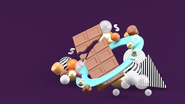 Chocolate bar among the colorful balls on the purple space