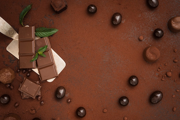 Chocolate bar candies truffles and cocoa powder with copy space